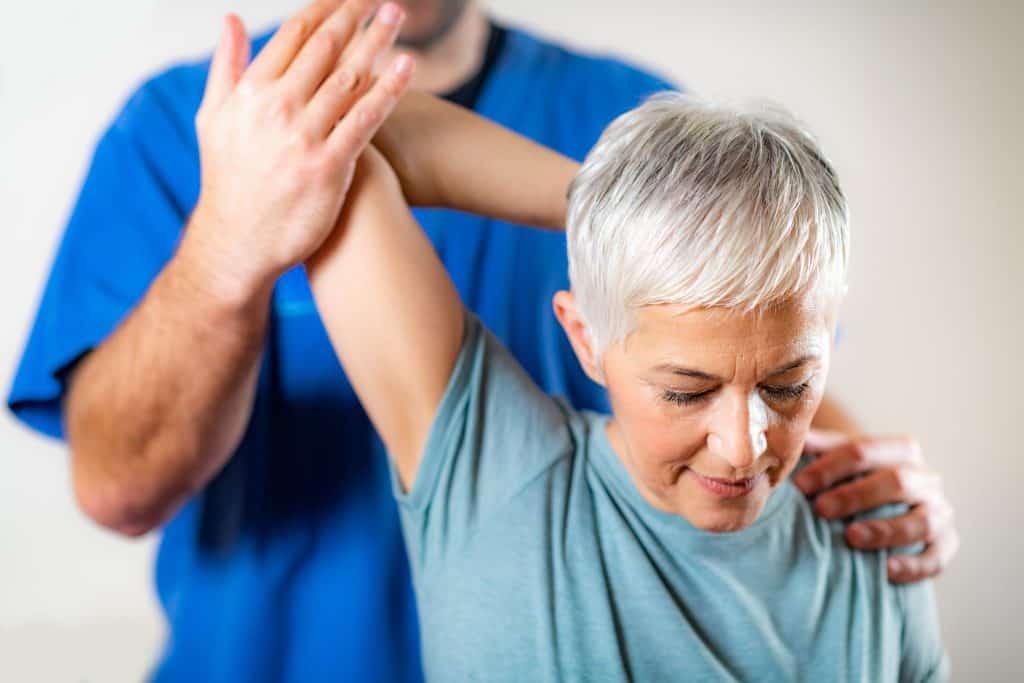 Therapist Checking Senior Woman's Arm